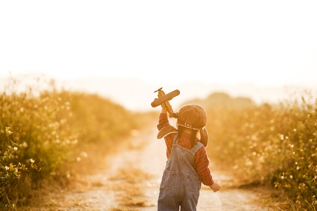 Child with toy airplane in nature at sunset