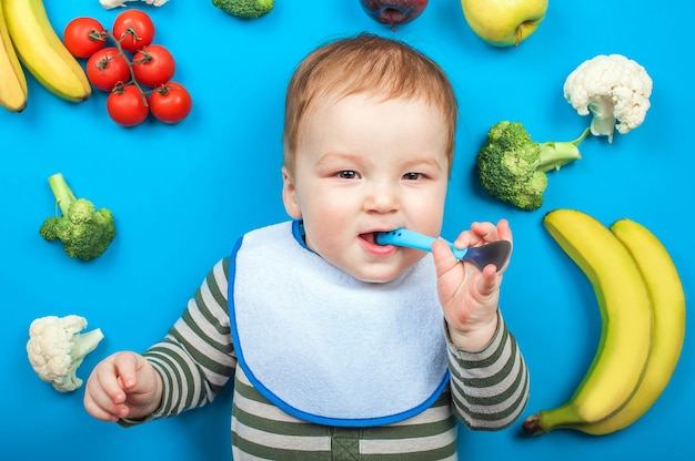 Ребенок с овощами и фруктами на синем фоне, здоровое детское питание. детское питание, бананы, брокколи, цветная капуста, кабачки, яблоки, помидоры