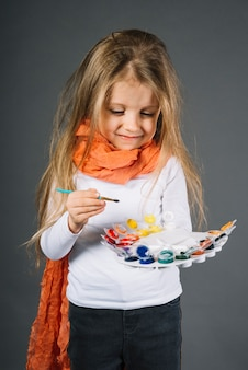 Child with water colors and brush in hands