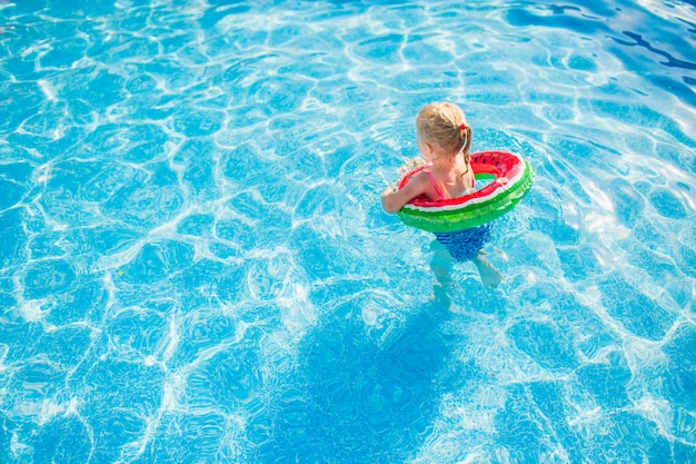 Child with watermelon inflatable ring in swimming pool. little girl learning to swim in outdoor pool. water toys and floats for kids. healthy sport for children.