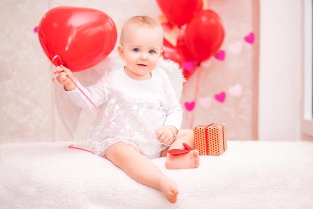 흰색 깃털 날개를 가진 아이는 발렌타인 데이의 상징 인 하트 모양의 빨간 풍선을 들고 있습니다.