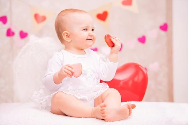 흰색 깃털 날개를 가진 아이는 심장 모양의 빨간 풍선을 보유하고 있습니다.