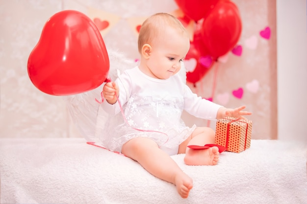 하트 모양의 빨간 풍선을 들고 흰색 깃털 날개를 가진 아이는 발렌타인 데이의 상징 인 선물 상자를 본다.