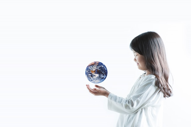 A child with a white   has the earth on his hand and is looking at it happily.