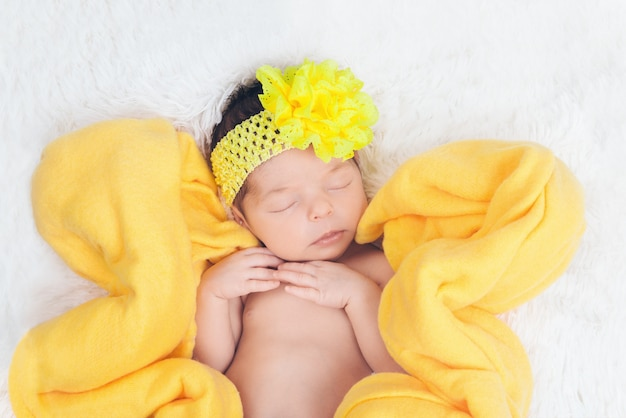 A child with a yellow bandage with a flower on his head in a yellow blanket in the shape of a flower