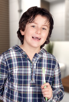 Child without some teeth brushing his teeth in the bathroom