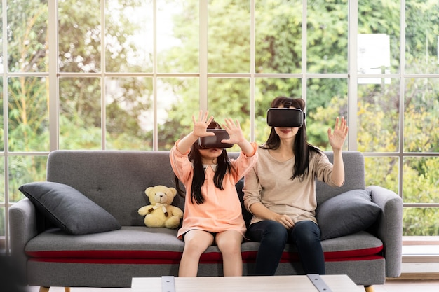 Child and woman with virtual reality headset smiling while sitting on sofa indoors at home