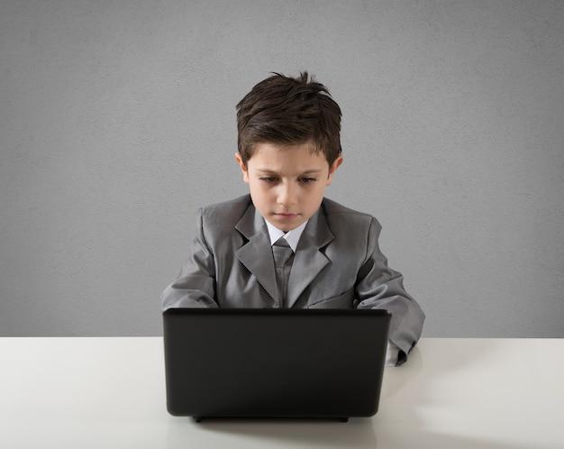 사업가로 컴퓨터에서 일하는 아이