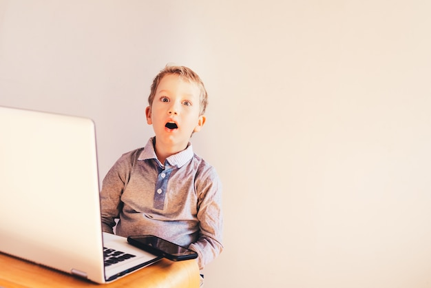 Child working business on his white laptop with surprise face.