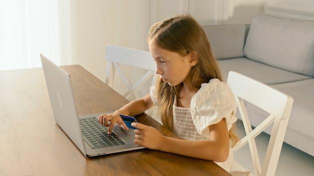 집에서 그녀의 노트북에서 일하고 아이의 신용 카드 현대 교육 데이터 보호 금융 교육으로 일부 작업을하는 아이