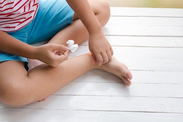 木の白い背景に子供の脚に傷や薬を服用