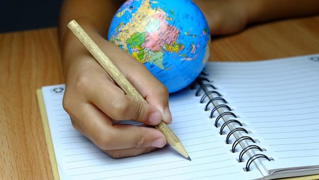 Ребенок записывает в блокнот с моделью globe