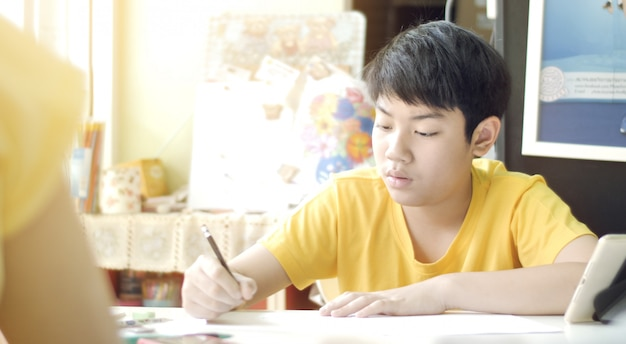 Child writes homework. children to doing home works on table in living room