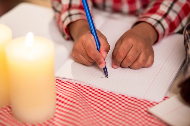 Child writes letter by candlelight. boy's hand writing by candlelight. young poet's revelations. sudden flow of thoughts.