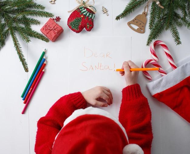 子供はサンタクロースに手紙を書きます。子供の手、紙、鉛筆、木の表面のクリスマスの飾り。