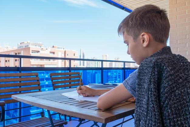 Ребенок пишет, делает домашнее задание на балконе