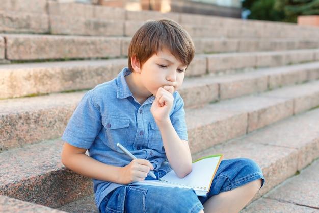 Ребенок пишет в записной книжке. дошкольный школьник делает домашнее задание. Premium Фотографии