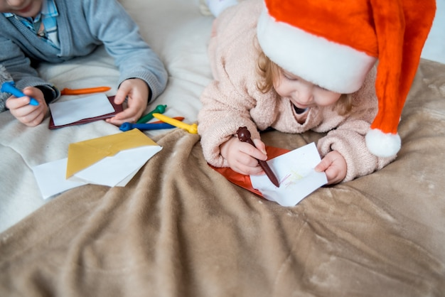 Child writing letter to santa claus letter in red hat. family on christmas. bright living room with komin on new year's eve.cozy warm winter evening at home
