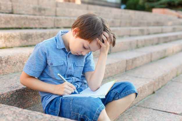 Child writing in a notebook. preteen schoolboy doing his homework.