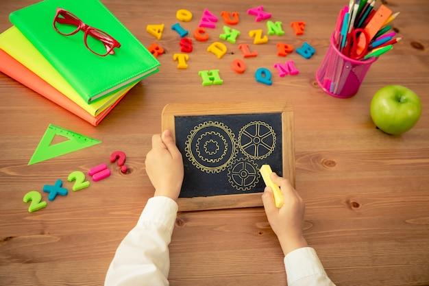 칠판에 쓰는 아이. 수업 시간에 나무 책상에 있는 학교 용품. 교육 개념입니다. 평면도