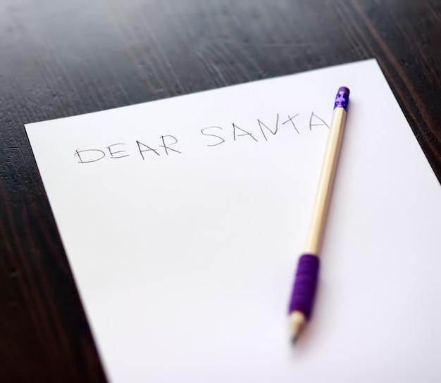 子供がサンタに手紙を書きます。子供は彼が受け取ることができる贈り物を夢見ています。