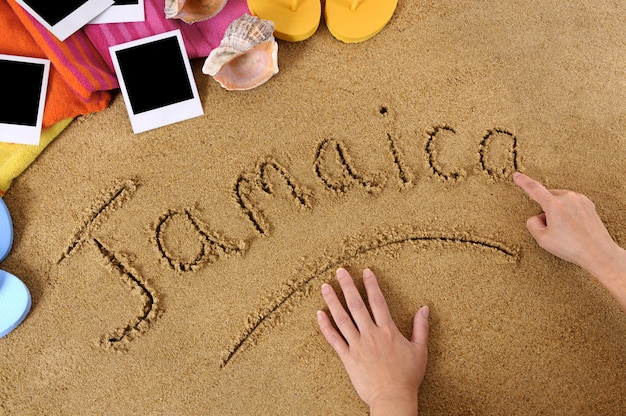Child writing the word jamaica in sand with towel, flip flops and blank photo prints