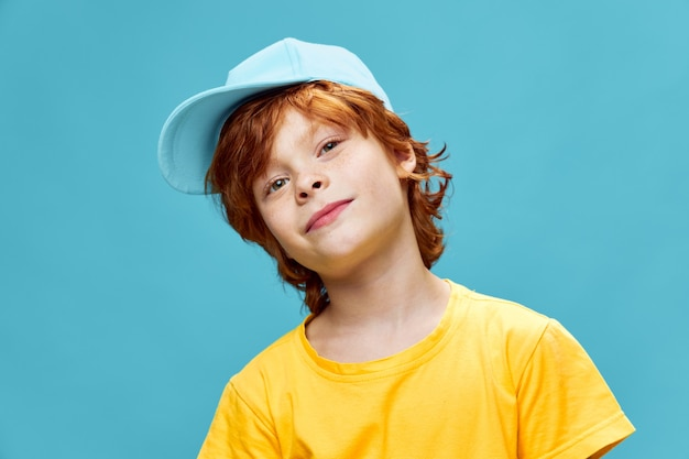 Child in a yellow t-shirt and a blue cap tilting his head to the side