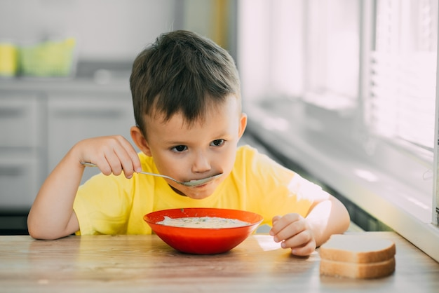 A child in a yellow t-shirt in  kitchen eating a national russian dish called okroshka