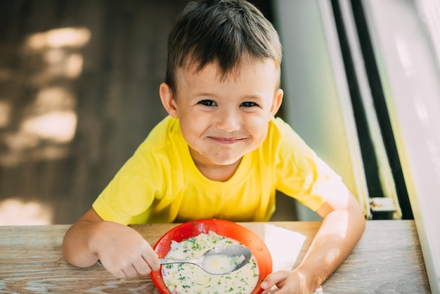 A child in a yellow t-shirt in the kitchen eating a national russian dish called okroshka