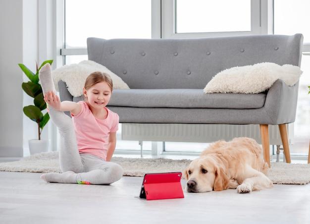 コロナウイルスの時間にタブレットを使ったチャイルドヨガオンラインエクササイズ。自宅で女の子とゴールデンレトリバー犬