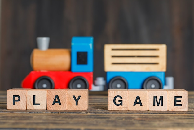 Childhood and activity concept with toy train, wooden cubes on wooden table side view.