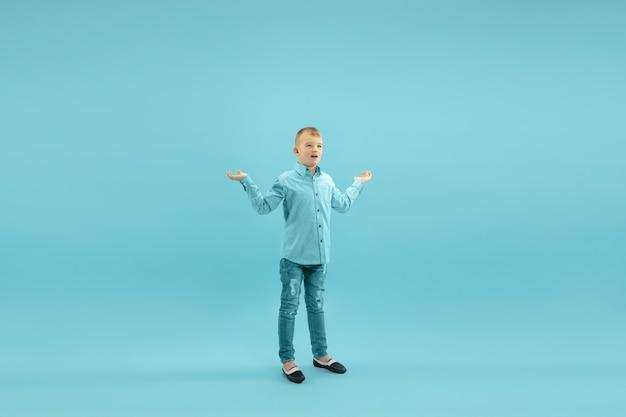 Детство и мечта о большом и знаменитом будущем симпатичного маленького мальчика, изолированного на синем