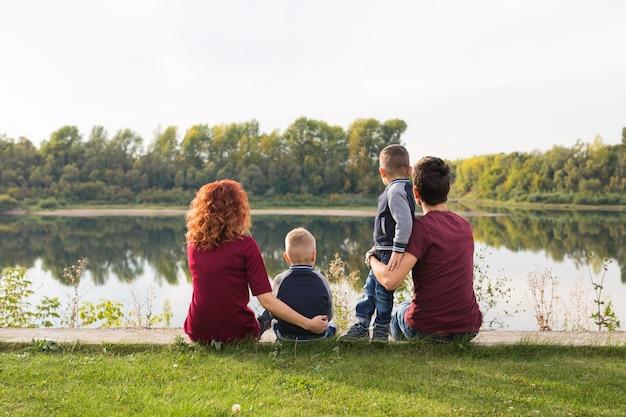 Концепция детства и природы - семья с маленькими сыновьями, сидящими на зеленой траве
