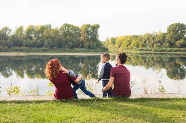 子供時代と自然の概念-緑の芝生の上に座っている幼い息子を持つ家族。