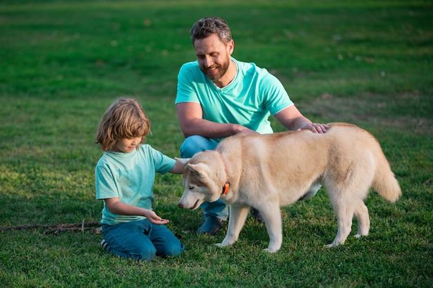 어린 시절과 부모가 된 어린이 개념 행복한 아버지와 아들이 애완견 야외 아이와 함께 놀고 있습니다.