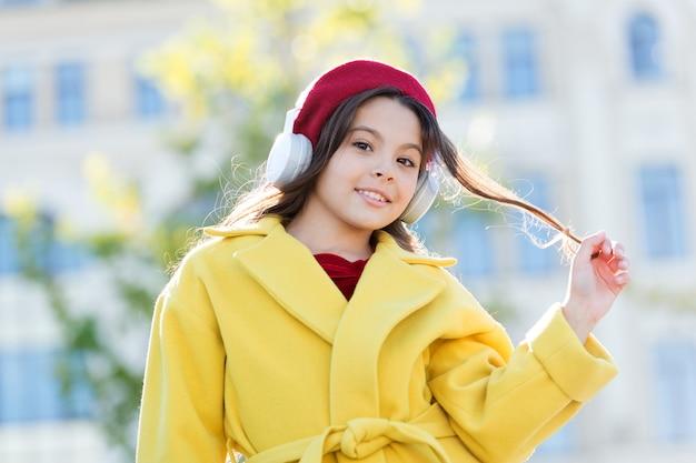 Детский и юношеский музыкальный вкус. маленькая девочка, слушающая музыку, наслаждается любимой песней. девушка с наушниками городской фон. обмундирование французского стиля девушки ребенка наслаждаясь музыкой. положительное влияние музыки.