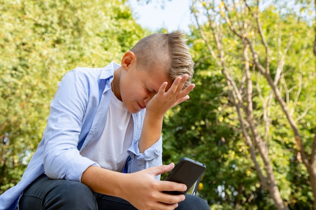 Детство, дополненная реальность, технологии и люди концепции - мальчик с расстроенным лицом смотрит в смартфон на открытом воздухе летом