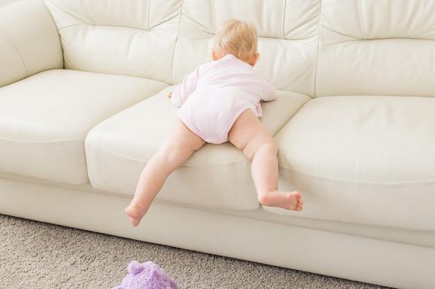 子供の頃、赤ちゃん時代と人々の概念-自宅のソファの近くで遊ぶ幸せな小さな女の赤ちゃん