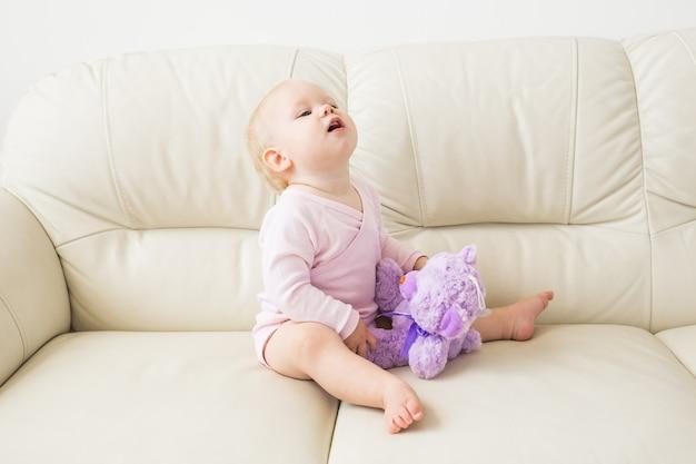 子供の頃、赤ちゃん時代と人々の概念-自宅のソファに座っている幸せな小さな女の赤ちゃん