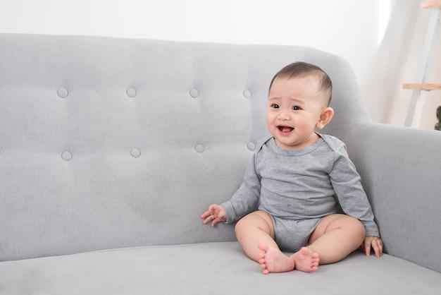 Детство, младенчество и люди концепции - счастливая маленькая девочка, сидящая на диване у себя дома