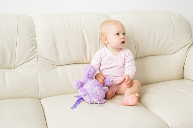 Childhood, babyhood and people concept - happy little baby girl sitting on couch at home