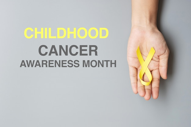小児がん啓発月間、生きている人々と病気をサポートするためのゴールドイエローリボンを手に持っています。子供のヘルスケアと世界対がんデーのコンセプト