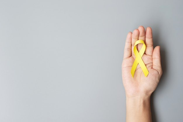 小児がん、肉腫、骨、膀胱、自殺予防意識月間、生きている人々と病気をサポートするためのゴールドイエローリボン。子供のヘルスケアと世界対がんデーのコンセプト