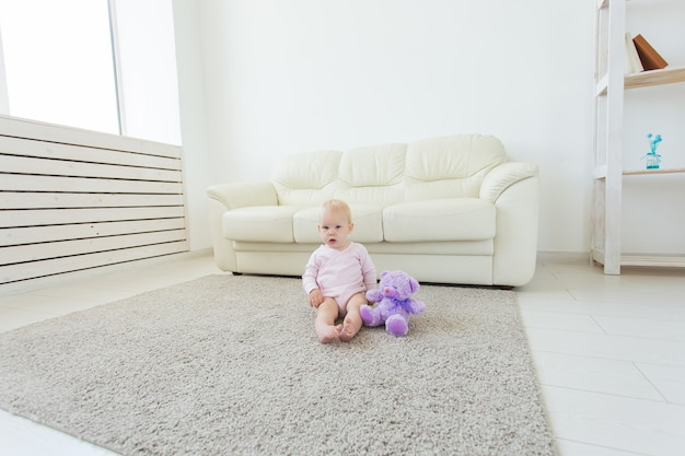 子供の頃、子供と赤ちゃんのコンセプト-床に座っている愛らしい金髪の赤ちゃん