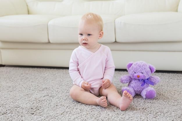 어린 시절, 어린이 및 유아기 개념 - 바닥에 앉아 있는 사랑스러운 금발 아기