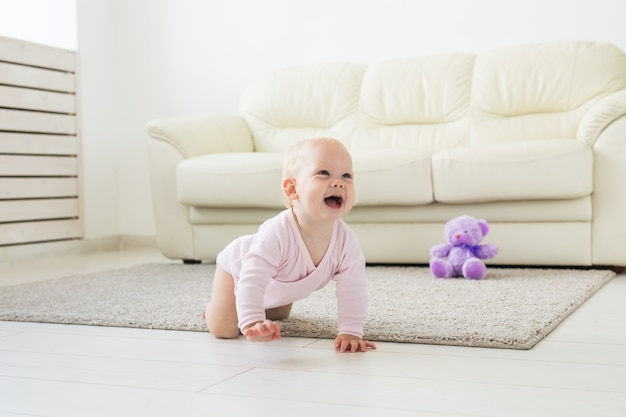 Childhood, children and babyhood concept - crawling funny baby girl indoors at home