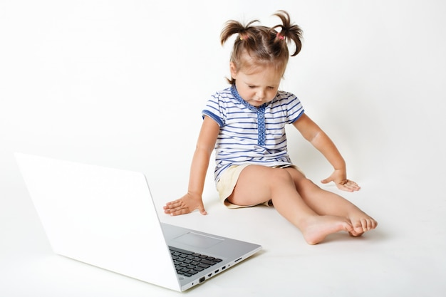 Childhood in digital age. attractive little kid sneezes and has eyes shut, looks down, sits near portable laptop computer, isolated over white wall. children and modern technologies concept