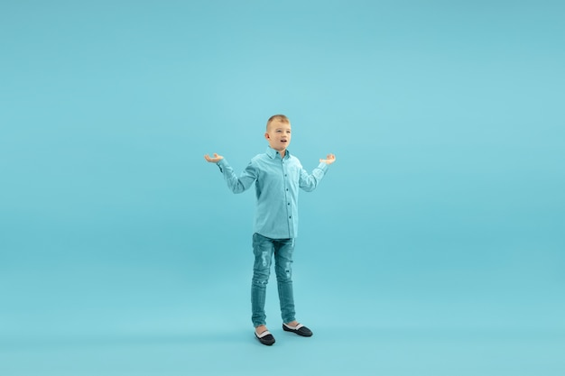 Childhood and dream about big and famous future pretty little boy isolated on blue