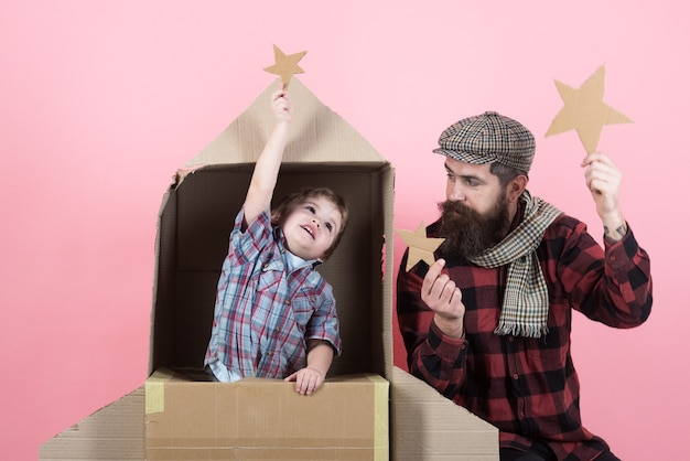 Childhood dream. father`s day. cardboard spaceship. kid playing with paper star in space rocket. happiness. space adventures. kid astronaut. stars.
