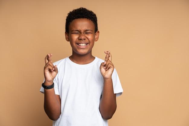 어린 시절의 꿈과 희망. 눈을 감고 손가락을 꼬고 서서 행운을 빌고 기적을 기다리는 사랑스러운 어린 소년의 초상화. 베이지 색 배경에 고립 된 실내 스튜디오 촬영